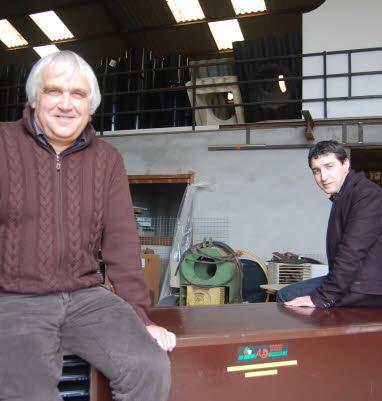 Assis sur un échangeur de chaleur, Michel Loaëc compte progressivement confier les rênes de sa société, Anavelec, à son fils Guillaume (en arrière-plan).